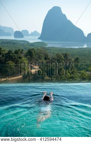 Happy Woman In White Swimsuit Swimming In Luxury Pool Hotel Against Phang Nga Bay Background, Touris