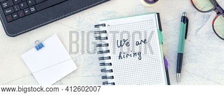 Banner With Words We Are Hiring. Job Recruiting Concept. Words We Are Hiring In Notebook On The Work