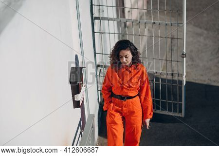 Young Prisoner Woman In Orange Suit At Jail Smoking. Female In Colorful Overalls Portrait.