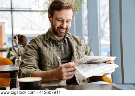 Unshaven smiling man in earphones reading newspaper while sitting in cafe
