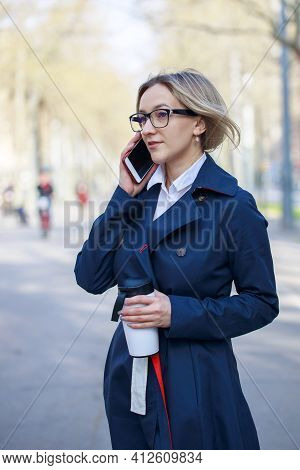 Confident Businesswoman Using Smart Phone On The Street. Blond Young Woman With Glasses, Coffee Cup