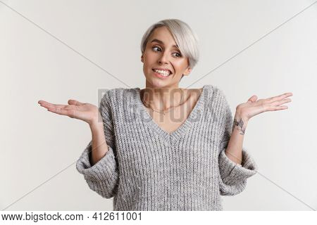 Perplexed beautiful silver girl showing and holding copyspace isolated over white background