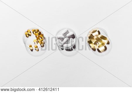 Vitamins Capsules On White Background, Top View, Copy Space. Food Supplements: Fish Oil, Omega 3, Om