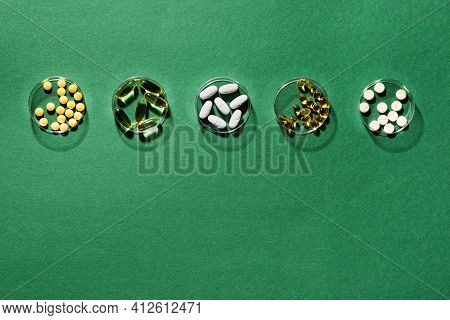 Vitamins Medicine Capsules On Green Background, Top View, Copy Space. Food Supplements: Fish Oil, Om