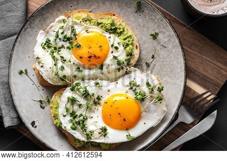 Avocado Egg Sandwiches For Healthy Breakfast. Whole Grain Toasts With Mashed Avocado, Fried Eggs And