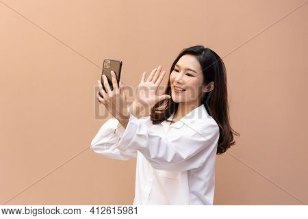 Portrait Of A Beautiful Young Asian Woman Making Facetime Video Calling With A Smartphone. She Makin