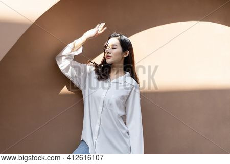 Portrait Of A Beautiful Asian Woman With Healthy Skin. She Uses A Sun Protection Hand That Hits Her