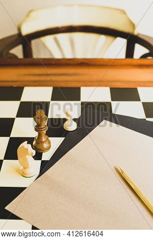 A Sheet Of Paper With Gold Pen And Three Chess Pieces Are On The Chess Table With Copy Space. Game O