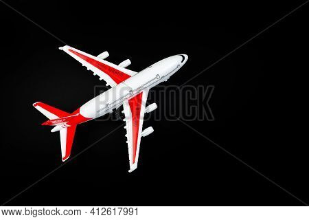 Plastic Model Airplane With Red Wings Against A Dark Background.