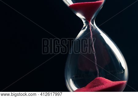 Sand Passes Through An Hourglass, Measuring The Travel Time Counting Down To The Deadline, Against A