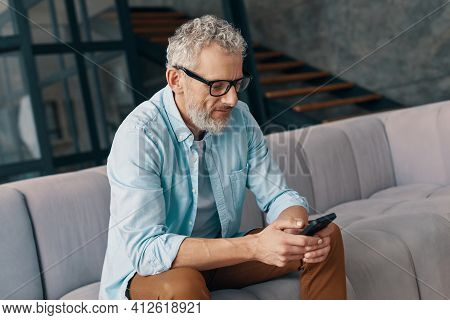 Senior Man In Casual Clothing And Eyeglasses Using Smart Phone While Sitting On The Sofa At Home
