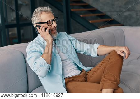 Good Looking Senior Man In Casual Clothing And Eyeglasses Talking On The Smart Phone While Sitting O
