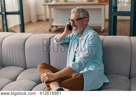 Happy Senior Man In Casual Clothing And Eyeglasses Talking On The Smart Phone While Sitting On The S