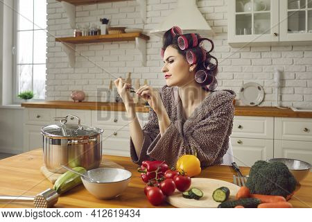 Beautiful Young Housewife In Hair Curlers Filing Her Nails Sitting At Kitchen Table