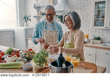 Happy Senior Couple In Aprons Preparing Healthy Dinner And Smiling While Spending Time At Home