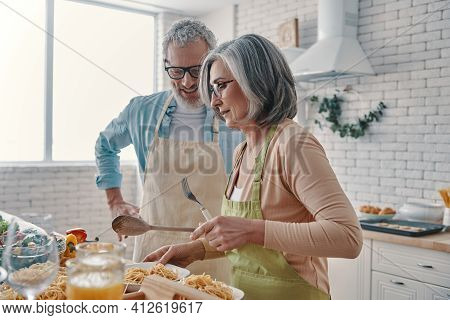 Senior Couple In Aprons Preparing Healthy Dinner And Smiling While Spending Time At Home