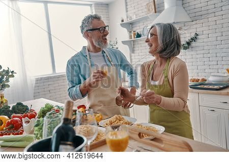 Modern Senior Couple In Aprons Preparing Healthy Dinner And Smiling While Spending Time At Home