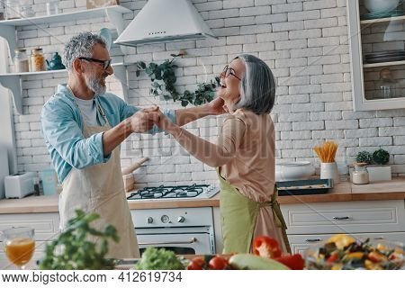 Playful Senior Couple In Aprons Dancing And Smiling While Preparing Healthy Dinner At Home