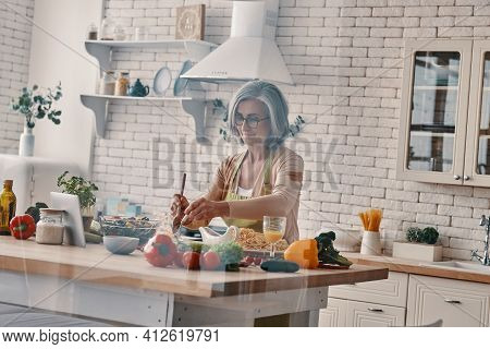 Busy Senior Woman In Apron Cooking Healthy Dinner While Spending Time At Home