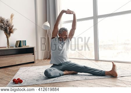 Senior Man In Sport Clothing Stretching While Sitting On The Floor Near The Window At Home