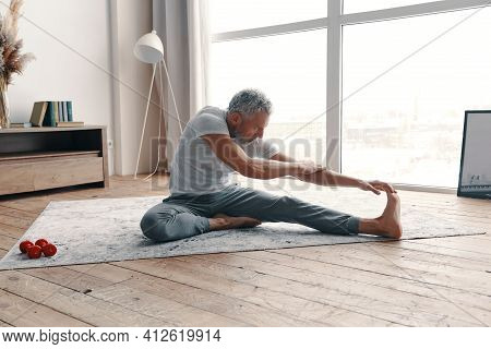 Well Shaped Senior Man In Sport Clothing Stretching While Sitting On The Floor Near The Window At Ho