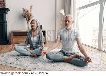 Active Senior Couple In Sports Clothing Exercising At Home Together
