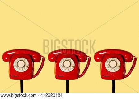 three red landline rotary dial telephones on top of three black tubular stands, on a yellow background, with some blank space on top