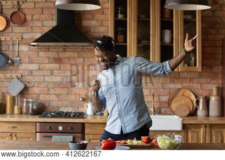 Joyful Afro American Man Singing At Kitchen Using Improvised Microphone