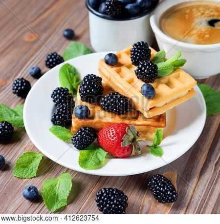 Close up view at belgian waffles served with strawberries, blueberries and blackberries on kitchen table wit a cup of coffee.
