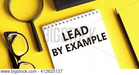 Notepad With The Text Lead By Example On A Yellow Background With Glasses, A Magnifying Glass And A