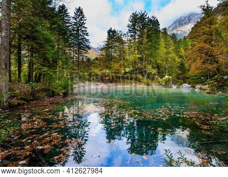 Travel to Slovenia. Julian Alps. Picturesque shallow lake with glacial greenish water, covered with fallen leaves. A light fog rises above the water. Autumn forest in a mountain valley
