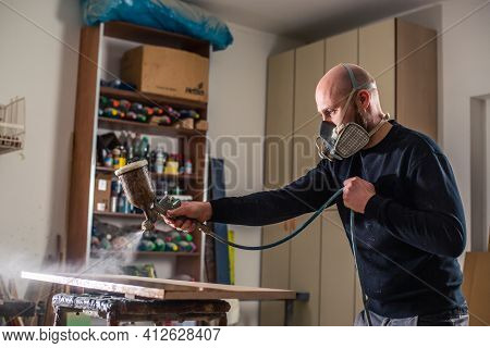 Joinery, Woodworking And Furniture Making, Professional Carpenter Varnishing A Wood In Carpentry Sho