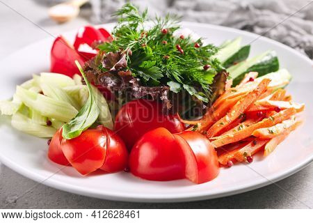 Raw Food - Fresh Vegetable Plate. White plate with healthy organic food on grey table. Tomato, Celery, Cucumber and Radish Vegetable and Fresh Greens. Produce, Healthy, Vegetarian rustic food concept