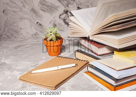 Stack Of Colorful Books, Notepad And Pen. An Open Book On A Stack Of Books. The Concept Of Education