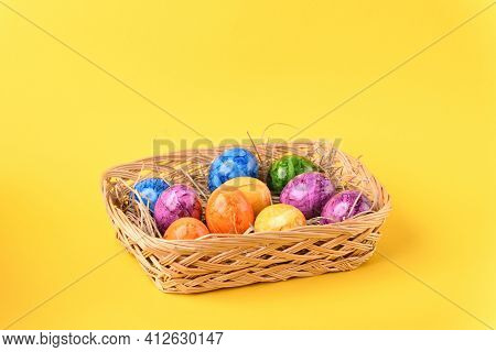 Colorful Easter Eggs In The Basket On The Blue Background.