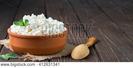 Farmer's Cottage Cheese In A Traditional Clay Bowl, Next To A Wooden Spoon, A Dark Wooden Background