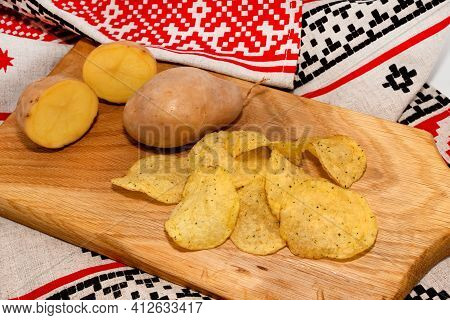 Potato Crisps With Spices And Potatoes On A Wooden Board. Potato Chips Close-up.