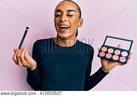 Hispanic man wearing make up and long hair holding makeup brush and blush smiling and laughing hard out loud because funny crazy joke.