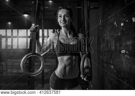 Portrait Of A Beautiful Woman In A Sports Uniform Near The Gymnastic Rings. Fitness, Bodybuilding, G