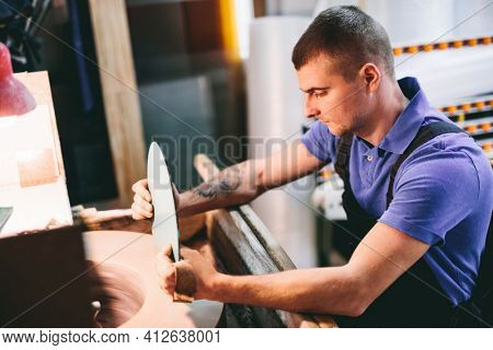 Glazier worker polishing glass in workshop. Industry and manufactory production