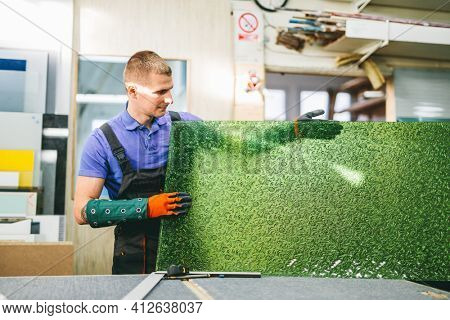 Glazier worker holding a green glass pane in workshop. Industry and manufactory production