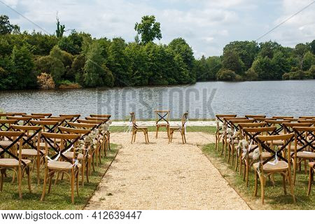 Wedding Ceremony On The Background Of Lake. Rows Of Wooden Chairs For Guests Standing On The Grass I