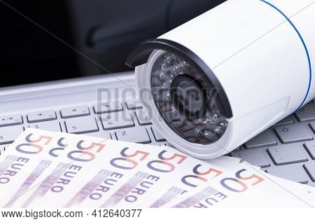 The Photo Shows A Security Camera With Banknotes On A Computer