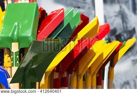 The Photo Shows Several Colorful Children's Shovels In The Sun