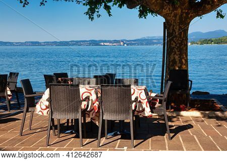 Chairs and tables of open air cafe overlooking Lake Garda, the largest lake in Italy and a popular holiday location on the edge of the Dolomites in Northern Italy