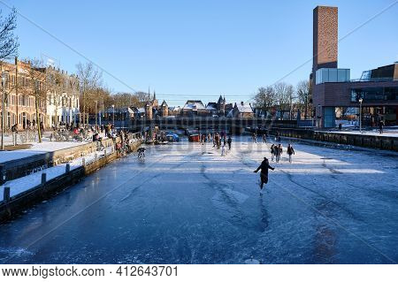 Amersfoort, Netherlands - Feb 13, 2021: People Ice Skating On Frozen Canal The Eem In City Center Of