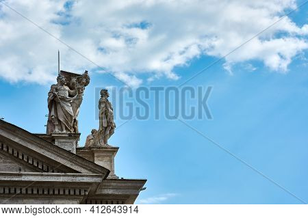 View Of Sculptures On Top Of The Tuscan Colonnades And Blue Cloudy Sky At St. Peter\'s Square In The