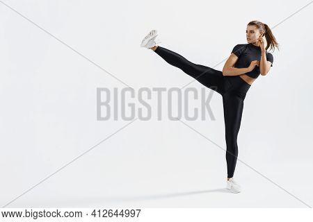 Confident Female Athlete Workout, Practice Leg Kicks, Kicking Air In Sportswear. Muscular Trained Wo