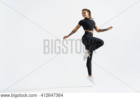 Woman In Sportwear Doing Jump Workout And Look Behind At Empty Space For Logo. Female Athlete With F