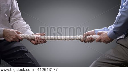 Two businessmen pulling tug of war with a rope concept for business competition, rivalry, challenge or dispute